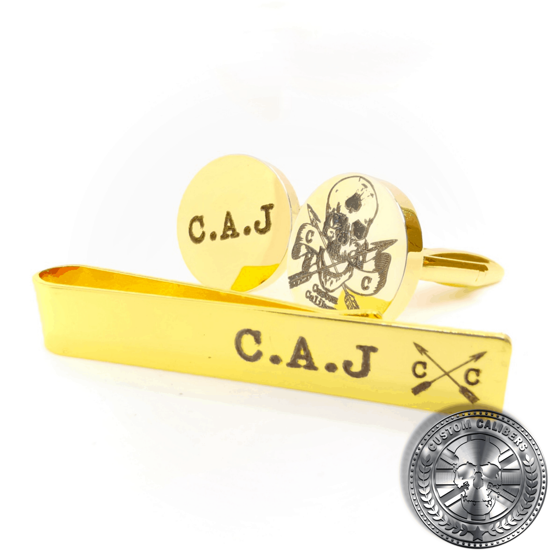 A close up shot of a solid brass Cuff link and tie clip set engraved with some initials and the custom calibers logo on the front
