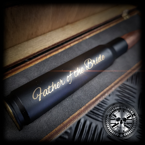 a close up shot of a matt black 50 caliber bullet bottle opener made by custom calibers engraved with father of the bride along the lengh of the bullet