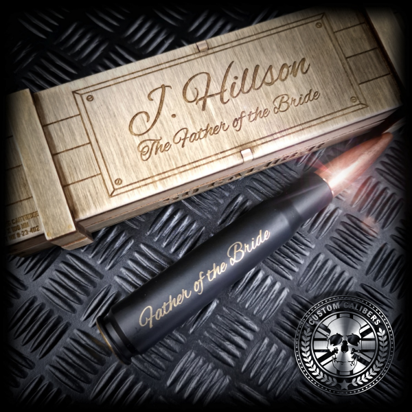 a mid range shot of a matt black 50 caliber bullet bottle opener made by custom calibers engraved with father of the bride along the lengh of the bullet with a matching engraved Wooden ammo crate gift box
