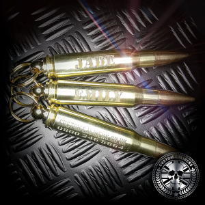 an awesome close up shot of three brass 308 bullet key chians engraved with different names on the side