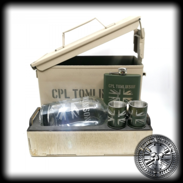 A proffessional shot of a custom calibers .50 cal ammo tin gift set showing the collection of gifts including a hip flask and two grenade shot glasses