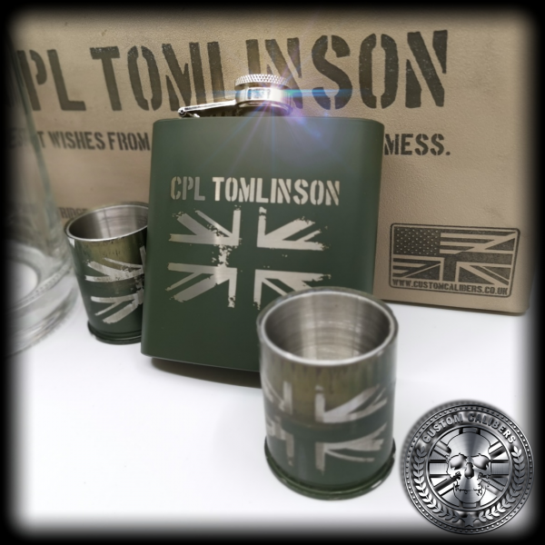 A close up of two custom calibers 40mm grenade shot glasses and a matching green hip flask. They have been engraved with the union jack design