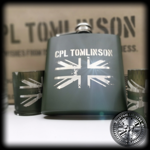 A close up of a custom calibers green hip flask. It has been engraved with a custom name