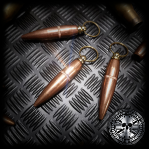 a close up shot of three 50 cal bullet head keychains
