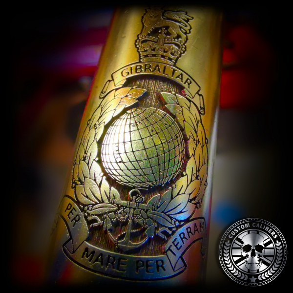 a close up macro shot of the royal marines military cap badge engraved into a solid brass bullet bottle opener