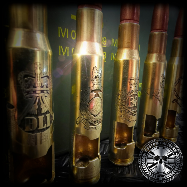 another side shot of five brass bullet bottle openers lined up next to each other showing different laser engraved military cap bages on the front