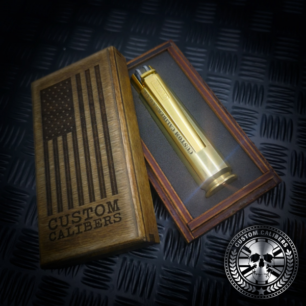 a nice photo of one of custom calibers .50 calibre bullet lighter next to a handmade wood gift box