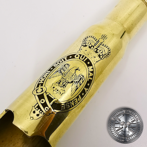 a great macro photo of a polished brass .50 caliber bullet bottle opener deep etched with a military crest