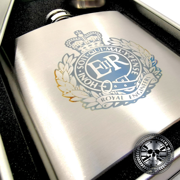 a brushed stainless steel hip flask engraved with a military crest