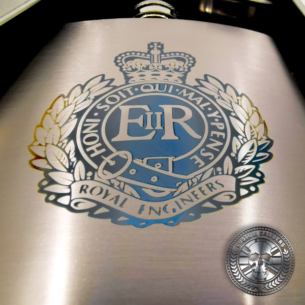 close up photo of a brushed stainless steel hip flask engraved with a military crest