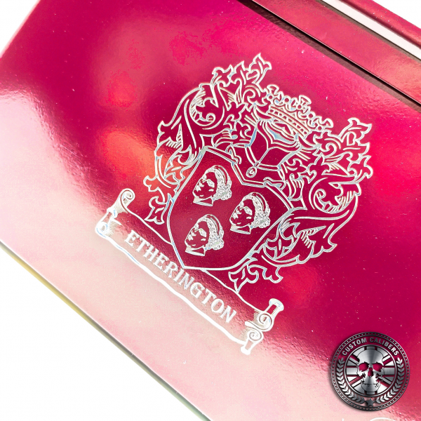 a close up photo of an engraved ammo tin powder coated in Airborne burgundy