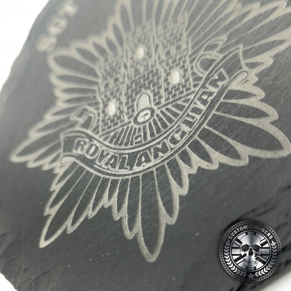 a close up of an engraved slate coaster with the royal anglian regiment crest