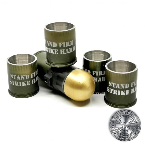 a quality photo of several 40mm GMg grenade shot glasses made from real once fired cases with engraved text