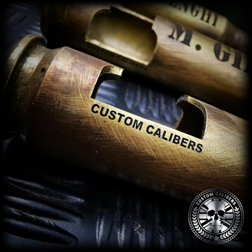 a great macro shot of one of custom calibers .50 cal bullet bottle openers with CUSTOM CALIBERS engraved into the side of the brass casing